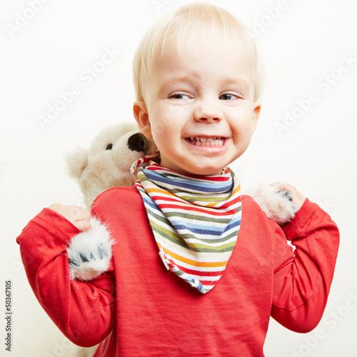 Kleines Kind trägt Teddybär huckepack
