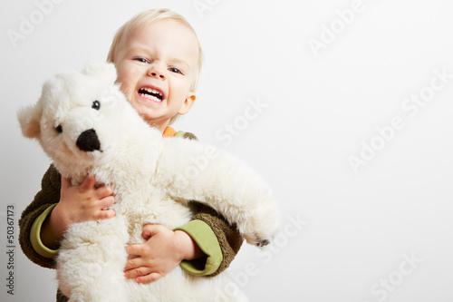 Junge hält grimmig sein Stofftier fest