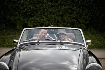 A young couple in a sports car with gardening tools in the back