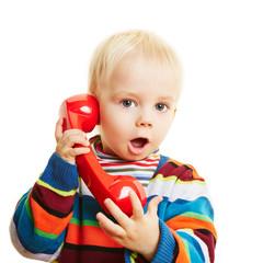 Kind beim Telefonieren mit roten Telefon