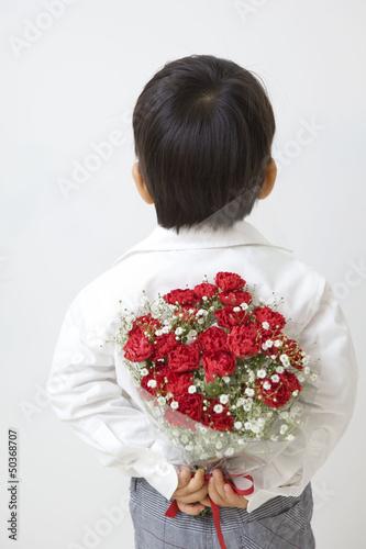 花束を持つ後姿の子供