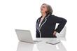 Ältere Arbeitnehmer - Frau hat Rückenschmerzen im Büro