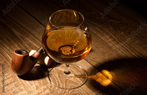 glass with brandy and tobacco pipe