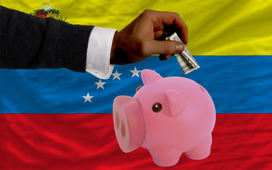 dollar into piggy rich bank and  national flag of venezuela