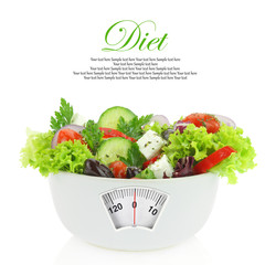 Diet meal. Vegetables salad in a bowl with weight scale