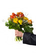 Mann im Anzug überreicht einen Blumenstrauss