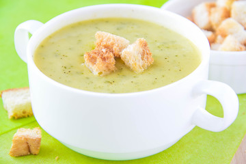 Zucchini cream soup with croutons in white cup