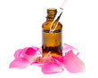 Fläschchen Rosenöl mit Rosenblättern und Pipette