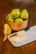 Bowl of Pears with Sliced Cheese and One Cut Pear