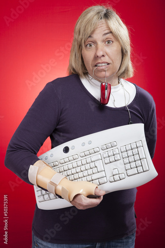 woman holding a keyboard with carpal tunnel injury