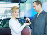 Key delivery between customer and mechanic in front of a car