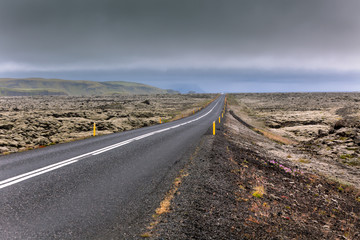 Highway through Iceland landscape at overcast day