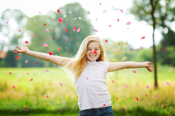 young girl throwing flower leaves