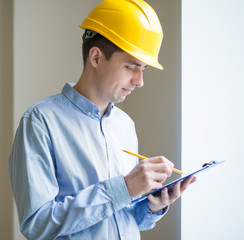 The builder in a helmet with a tablet