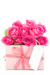 Bouquet of beautiful pink roses next to a pink gift with a blank