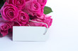 Bouquet of beautiful pink roses with an empty card on a table