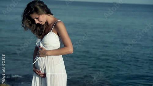 Pregnant woman standing on the seashore, slow motion shot at 120