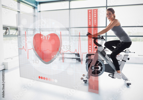 Young girl doing exercise bike with futuristic interface
