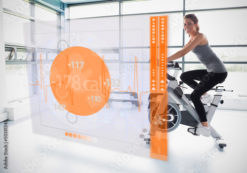 Young girl doing exercise bike with futuristic interface showing