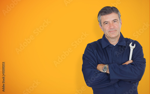 Mature mechanic standing in front of yellow background