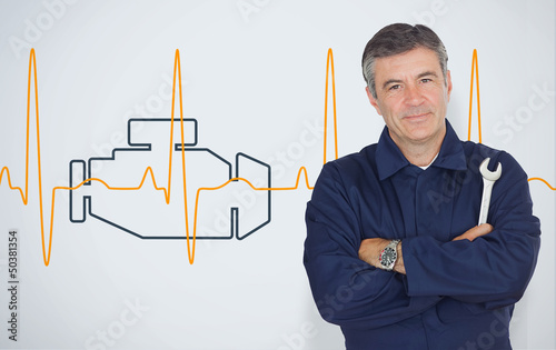 Mature mechanic standing in front of an engine background