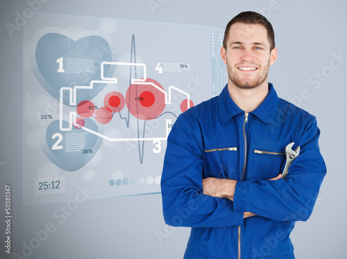 Portrait of a young mechanic with futuristic interface next to h
