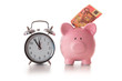 Alarm clock and piggy bank with fifty euro sticking out