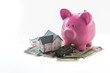 Piggy bank toy car and miniature home resting on pile of dollars