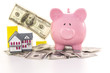 Piggy bank beside graph and miniature house