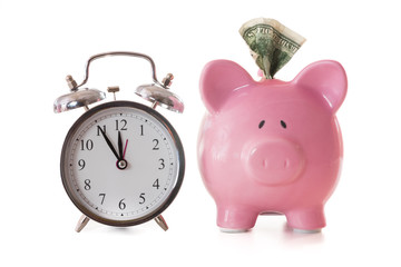 Dollar note sticking out of piggy bank beside alarm clock