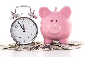 Pink piggy bank beside alarm clock on dollars