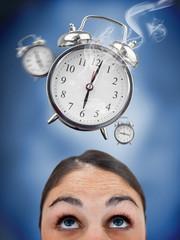 Woman looking up at ringing alarm clocks