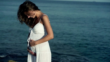 Pregnant woman standing on the seashore, slow motion shot at 240
