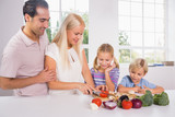 Family cutting vegetables together