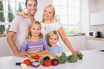 Smiling posing family cutting vegetables together