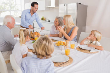 Smiling father proposing a slice of turkey