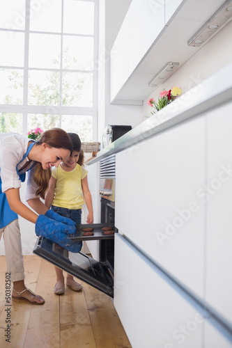 Mother taking cookies out of the oven