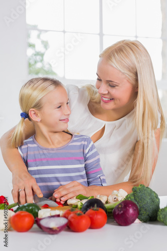 Mother teaching cutting vegetables