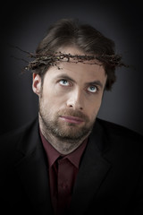 Contemporary man in a crown of thorns - unhappy worker concept