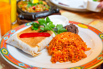 Mexican burritos with beef, melted cheese and rice