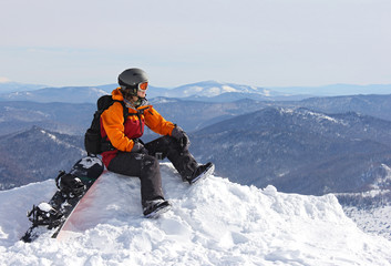 girl with snowboard on top of mountain