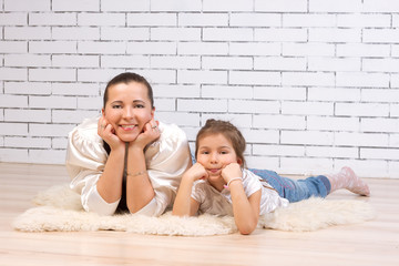 Mother and 5-year-old daughter lying on the floor