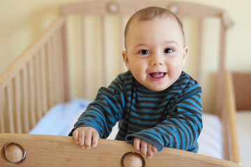 Baby standing in cot