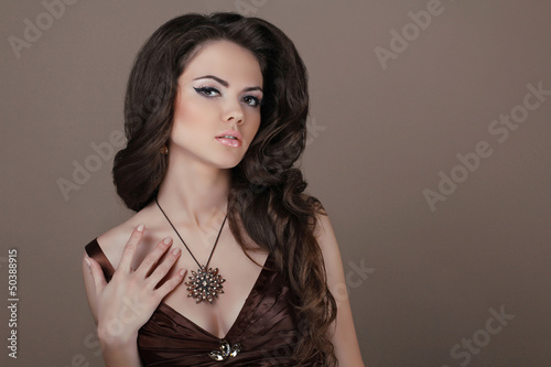 Woman with beauty long brown hair. Jewelry and Beauty. Fashion a