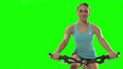 Young woman biking front shot on green screen.