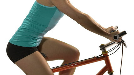 young woman's legs while biking in front of a white background.