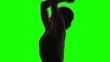 Silhouette of a Young woman dancing. Green screen in slow motion