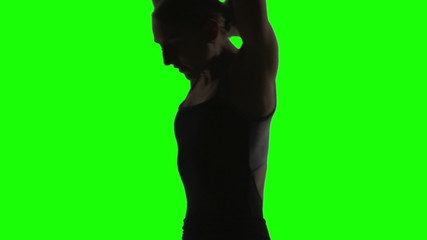 Silhouette of a Young woman dancing in front of a green screen.
