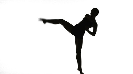 Silhouette of Young woman dancing in front of white background.