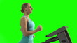 Young woman running on treadmill in front of green screen.